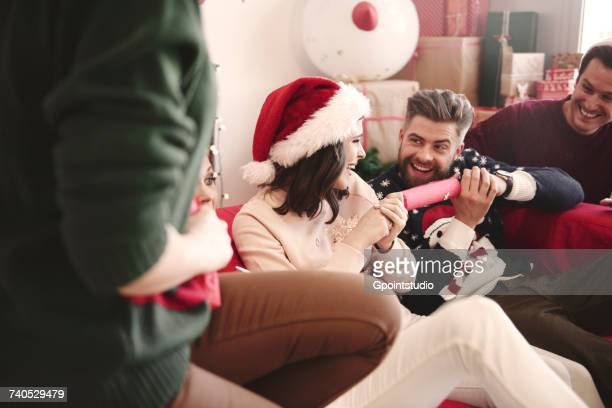 Young adult friends pulling christmas crackers on sofa at christmas party