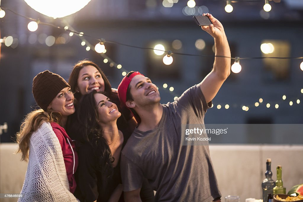 Young adult friends taking self portrait at party : Stock Photo