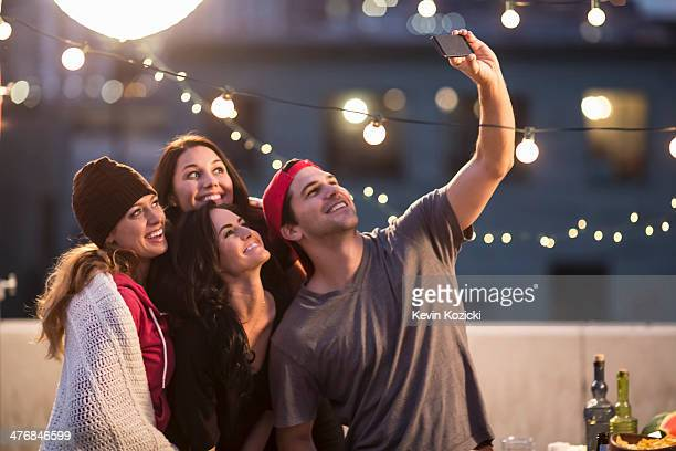 Young adult friends taking self portrait at party