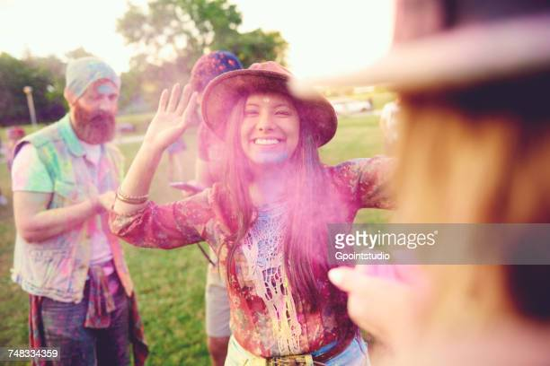Young adult friends throwing coloured chalk powder at festival