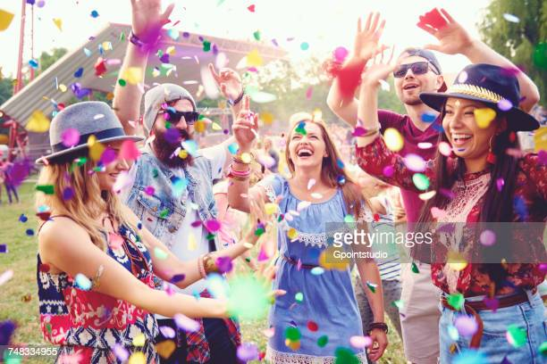 young adult friends throwing confetti at festival - multi colored hat stock pictures, royalty-free photos & images