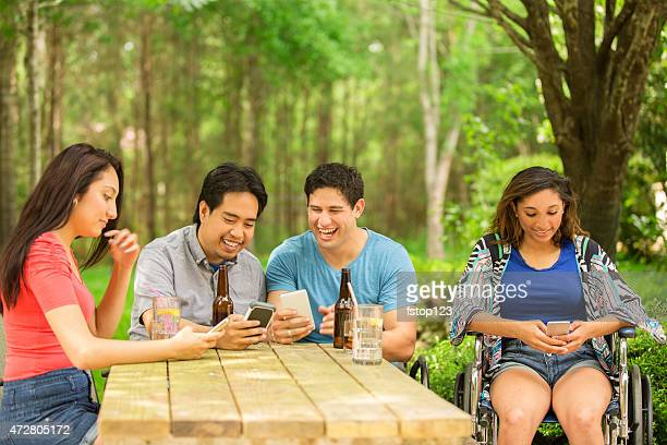 young adult friends view social media on cell phones. outdoors. - paraplegic woman stock photos and pictures