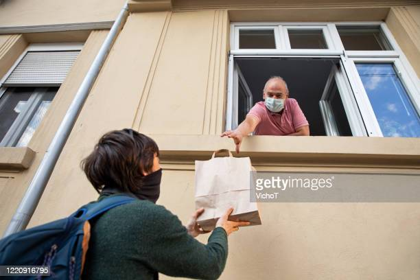 young adult giving a bag with shopping to his father through the window - distant stock pictures, royalty-free photos & images