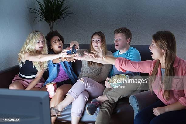 Adulto joven luchando por grupo televisor con Control remoto.