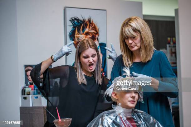 young adult hairdresser content with customer's hair - finishing stock pictures, royalty-free photos & images