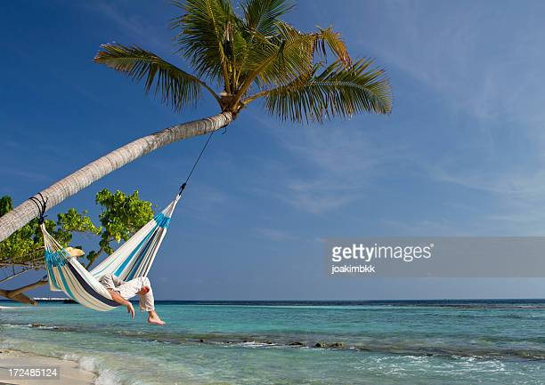 Young adult hammock napping in paradise
