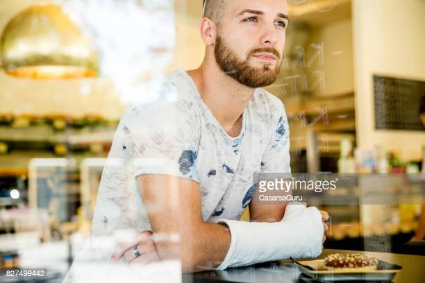 young adult handsome man in bar - broken arm stock pictures, royalty-free photos & images