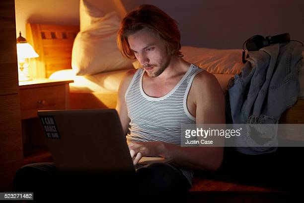 Young adult handsome man using his laptop in bedroom