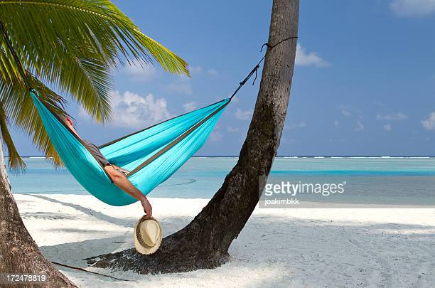 Young adult having a nap in a beach hammock