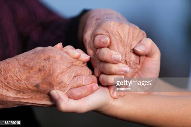 Young adult helping senior women, holding hands