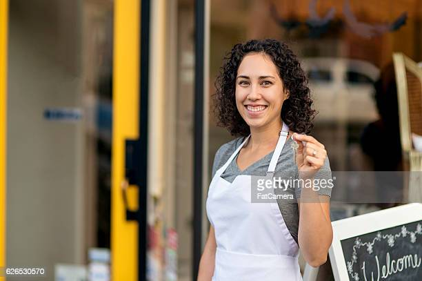 Young adult Hispanic female business owner holding keys to store