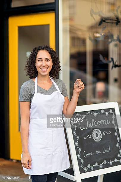 Young adult Hispanic female business owner holding up keys