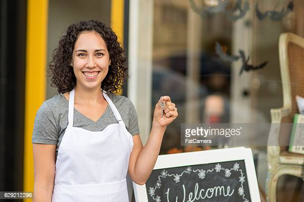 Young adult hispanic woman holding keys to her small business