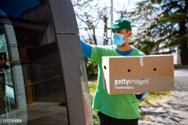 young adult home delivery man working during coronavirus pandemic - stock photo - essential services stock pictures, royalty-free photos & images