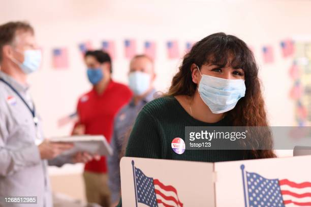 young adult, latin descent woman votes in usa election wearing mask. - voting stock pictures, royalty-free photos & images