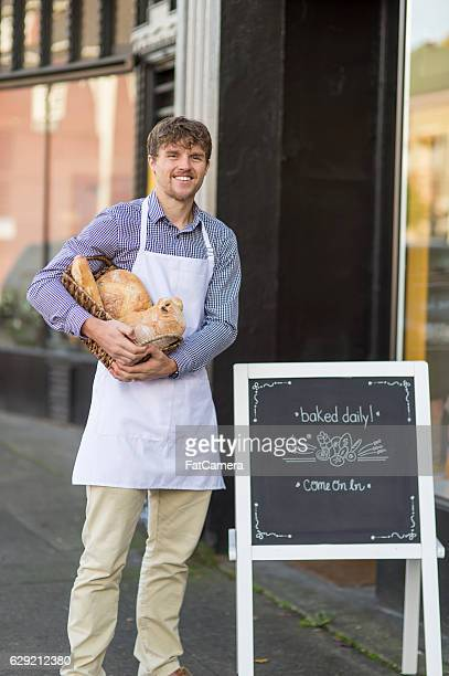 Young adult male baker standing outside his small downtown business