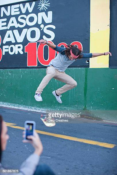 Young adult male being photographed on smartphone doing skateboarding trick
