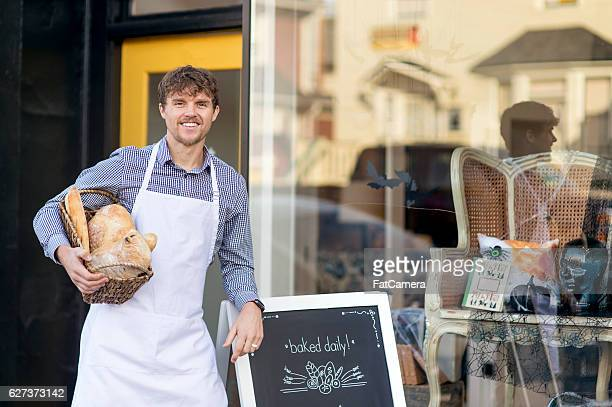 Young adult male business owner holding basket of baked goods
