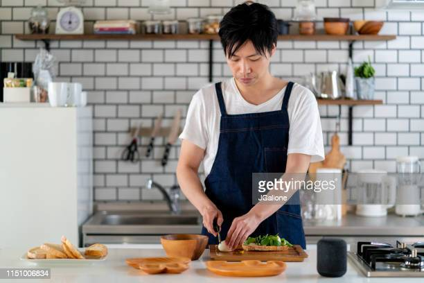 young adult male cooking at home alone - jgalione stock pictures, royalty-free photos & images
