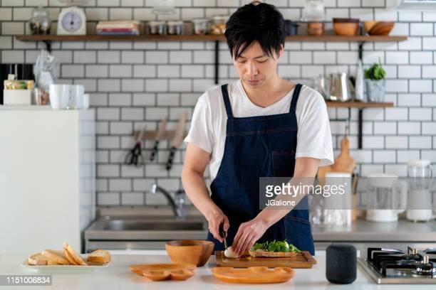 一人で家で若い大人の男性の調理 - 料理 ストックフォトと画像