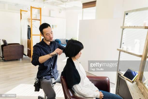 女性の髪を吹く若い成人男性の脱毛スタイリスト オーナー