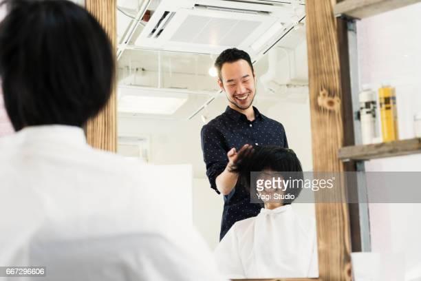 若い成人男性の脱毛スタイリスト オーナー切断女性の髪