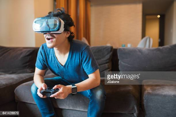 young adult male playing virtual reality game - jgalione stock pictures, royalty-free photos & images