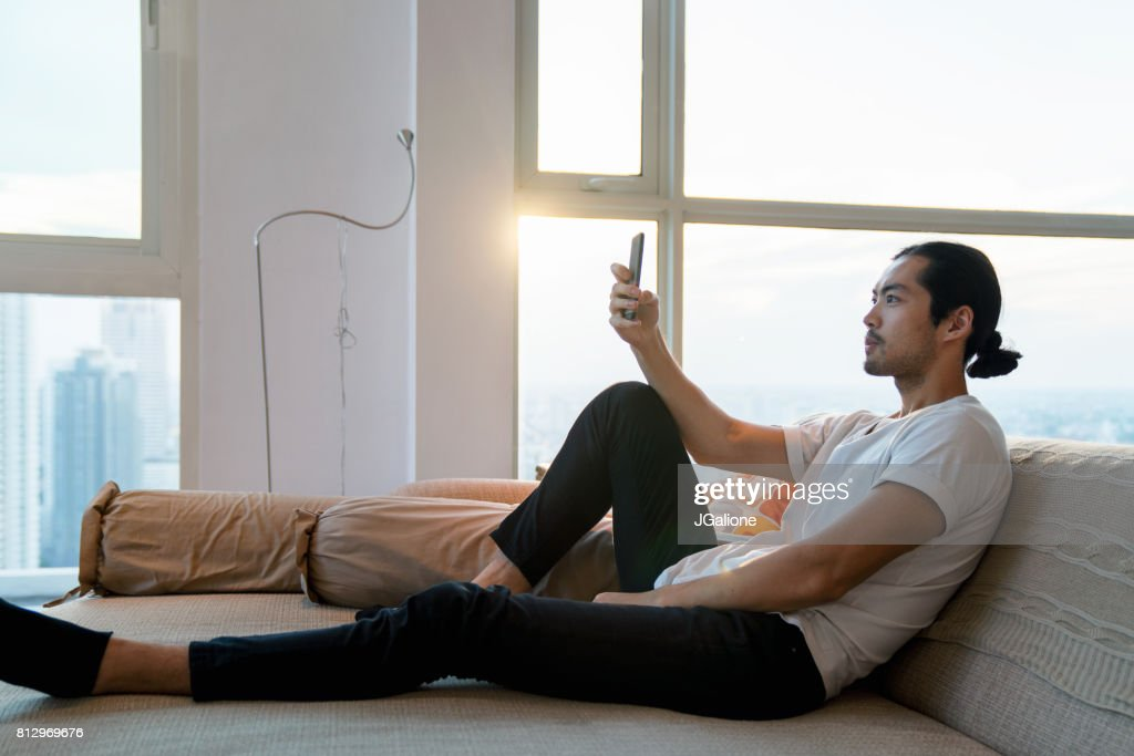 Young adult male relaxing at home and checking his phone : Stock Photo