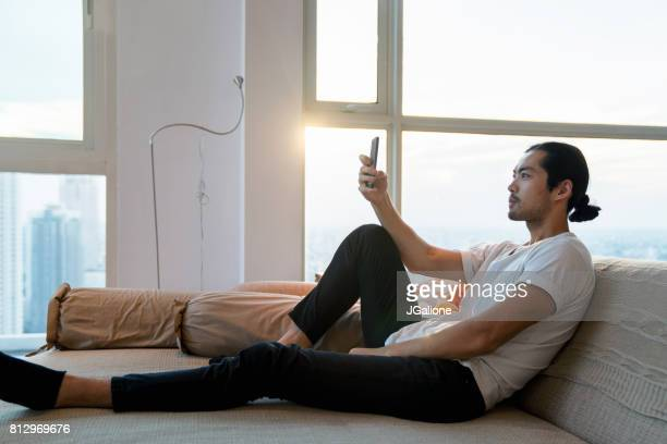 Young adult male relaxing at home and checking his phone