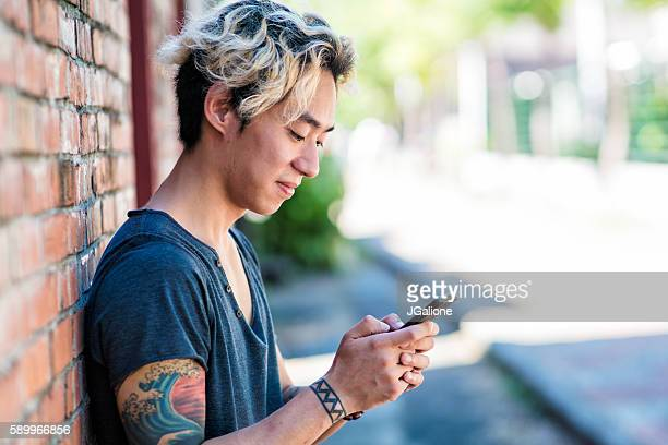 Young adult male relaxing outside using a smartphone