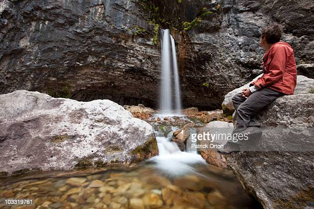 A young adult male sits next to waterfall in Colorado.