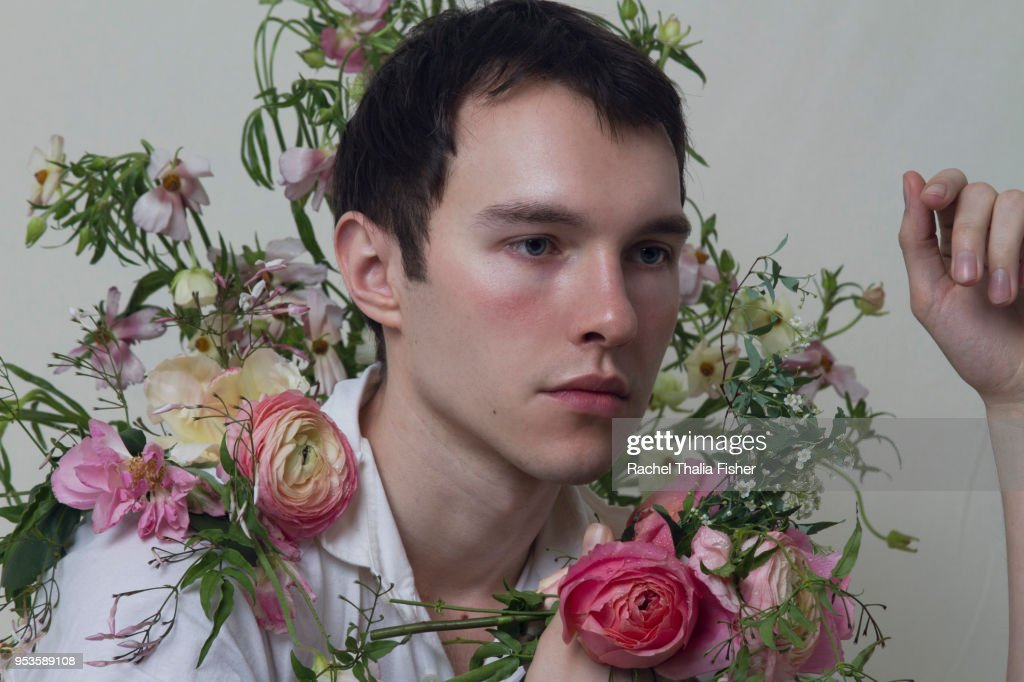 Young adult male  surrounded by flowers : Stock Photo