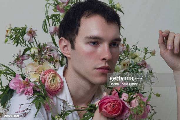 Young adult male  surrounded by flowers