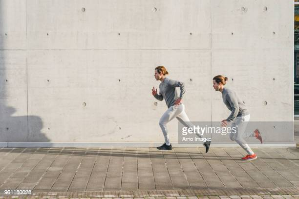 Young adult male twins running together, running up sidewalk