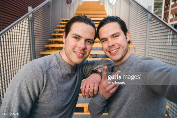 Young adult male twins training together, stairway self portrait