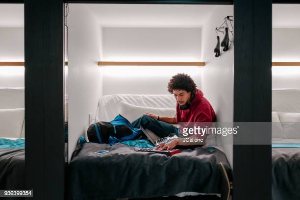 Young adult male using audio equipment in a capsule hotel