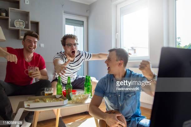 giovani maschi adulti che guardano la partita di basket e bevono birra a casa - spettatore foto e immagini stock