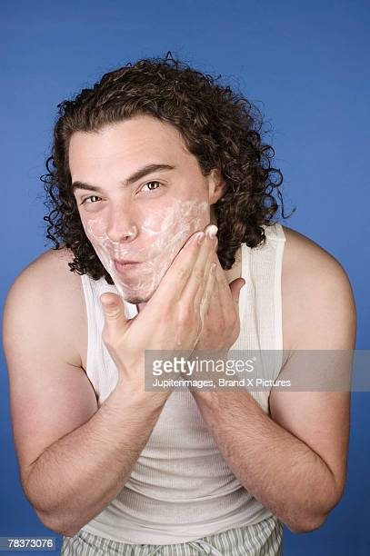 Young adult man applying shaving cream