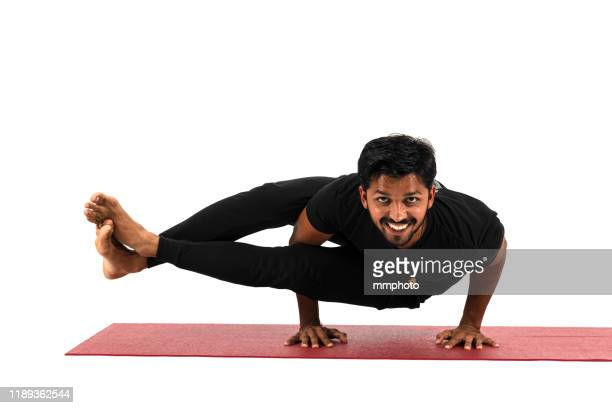 young adult man doing eight-angle pose, astavakrasana - yogi stock pictures, royalty-free photos & images