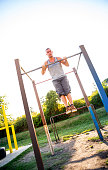 young adult man doing pullups outdoors