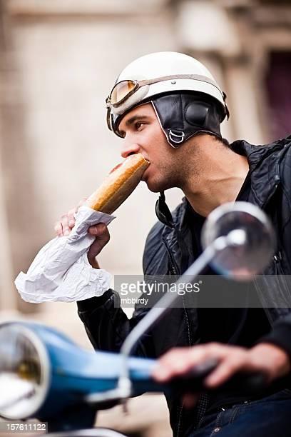 Adulto joven hombre comiendo baguette en motoneta
