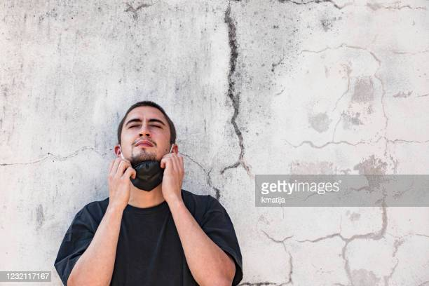 young adult man enjoying removing his protective face mask - removing stock pictures, royalty-free photos & images