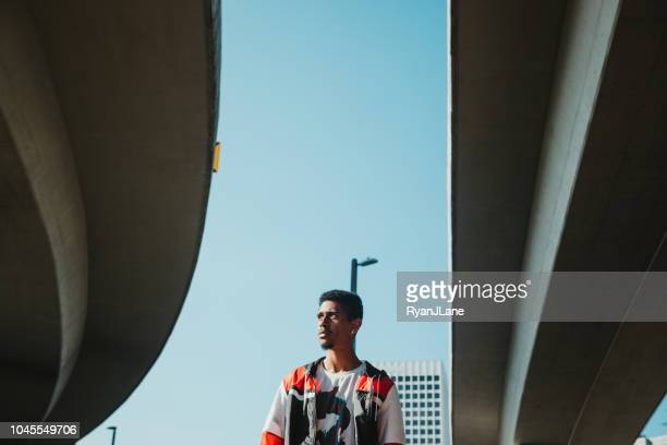 young adult man in urban city setting - wide angle stock pictures, royalty-free photos & images
