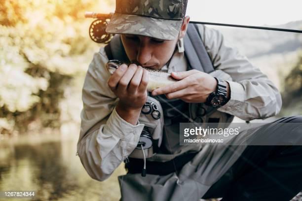 若い大人の男は速い山の川で一人で釣りをしています。アクティブな人々とスポーツフライフィッシングコンセプト。 - アンコウ ストックフォトと画像