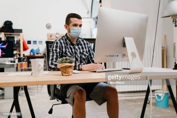 young adult man is working at home with a desktop pc - shorts stock pictures, royalty-free photos & images