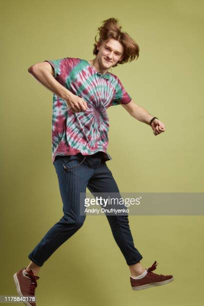 young adult man jumping for joy - percussion instrument stock pictures, royalty-free photos & images