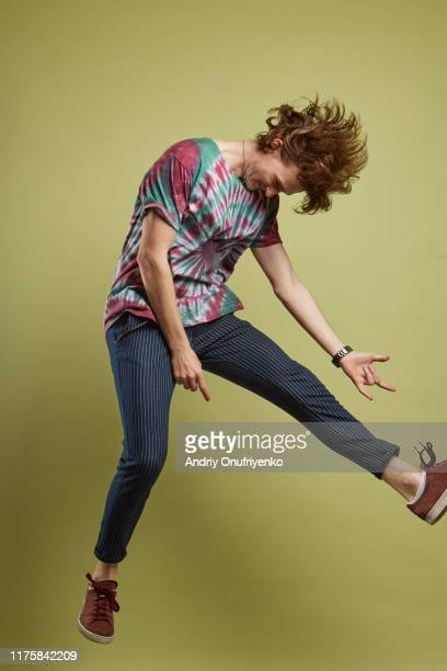 young adult man jumping for joy - modern rock stock pictures, royalty-free photos & images