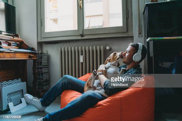 young adult man listening to music in his bedroom with his dog - listening stock pictures, royalty-free photos & images