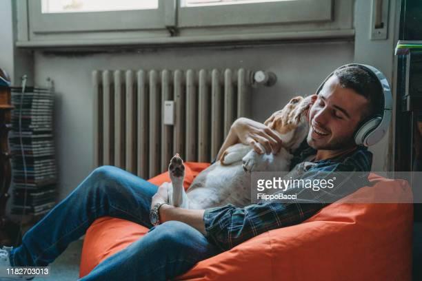 giovane adulto che ascolta musica nella sua camera da letto con il suo cane - dog pad foto e immagini stock