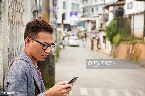 Young adult man on cell phone in urban city street.